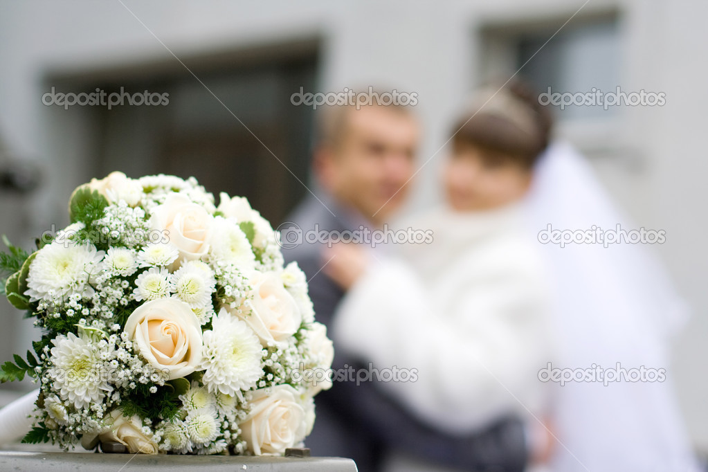 Wedding bouquet in the foreground, the background newlyweds  Stock Photo #2583219