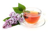 Blossoming branch of a lilac and tea — Stock Photo