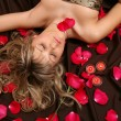 The girl and petals of roses — Stock Photo