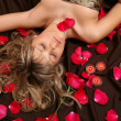 Stock Photo: The girl and petals of roses