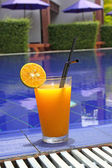 Orange cocktail stands on edge of pool — Stock Photo