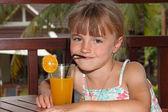 The girl drinks orange juice — Stock Photo