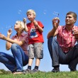 Happy family blowing soap bubbles — Photo