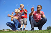Happy family blowing soap bubbles — Stok fotoğraf