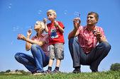 Mutlu bir aile sabun köpüğü üfleme — Stok fotoğraf