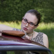 Beautiful girl in glasses at the car — Stock Photo