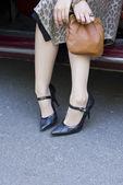 Piernas femeninas en un zapato de tacón alto en un coche — Foto de Stock
