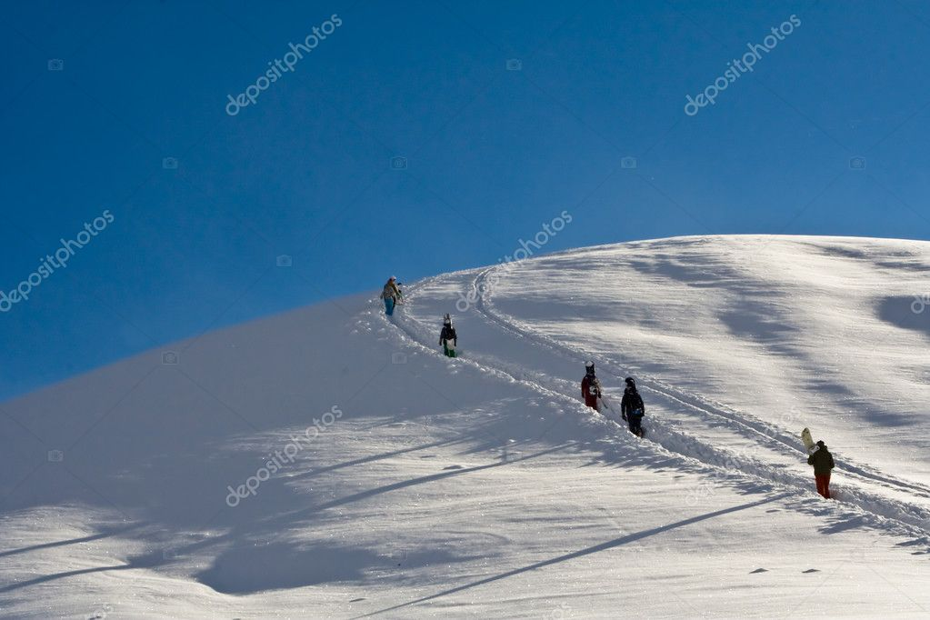 Snowboarders walking up the mountain in snow — Stock Photo #1286205