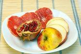 Sliced fruits on white dish — Stock Photo