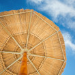 Beach umbrella and cloudy sky — Stock Photo