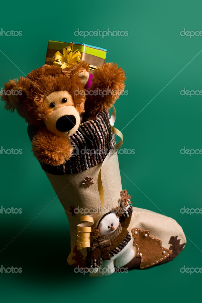 Christmas boot with toys and gift over green background — Zdjęcie stockowe #1229912