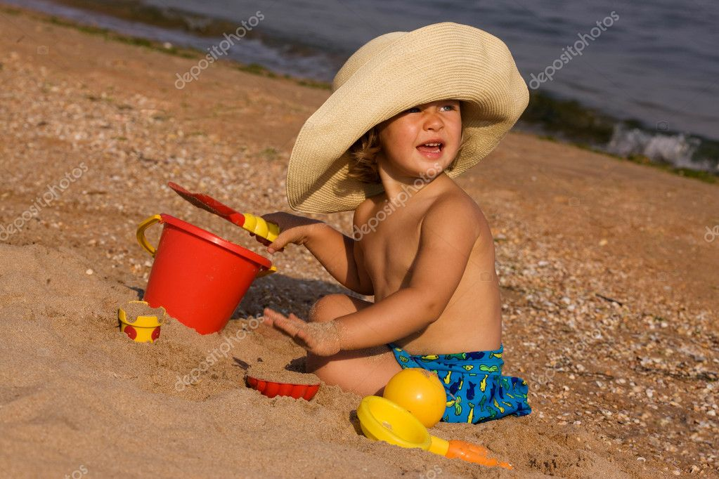 Little girl in the bonnet plaing with sand, happy childhood  Stock Photo #1312923