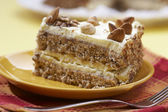 Cake with almonds and nut on the yellow plate — Stock Photo