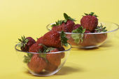 Strawberry bowl over yellow — Stock Photo