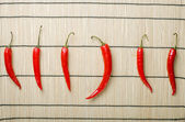 Five chili peppers lay at right directio — Stock Photo