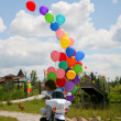 Little boy on motobike with helium bubbl — Stock Photo