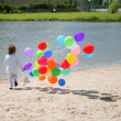 Stock Photo: Little boy runs with helium bubbles on s