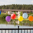 Helium baloons at bridge with lake and h — Stock Photo