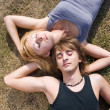 Couple lying in grass with closed eyes — Stock Photo