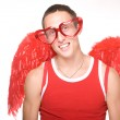 Young man smiles in red heart-glasses wi — Stock Photo
