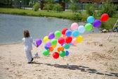 Mały chłopiec biegnie z balonów helem na s — Zdjęcie stockowe
