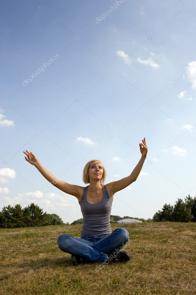 Happy woman with hands up, sitting on meadow. — Stock Photo #1273598