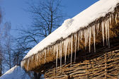 Icicles on a roof of cottage across blue sky — Stock Photo