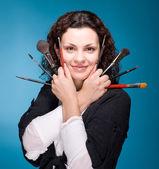Stylist with make up brushes on blue background — Stock Photo
