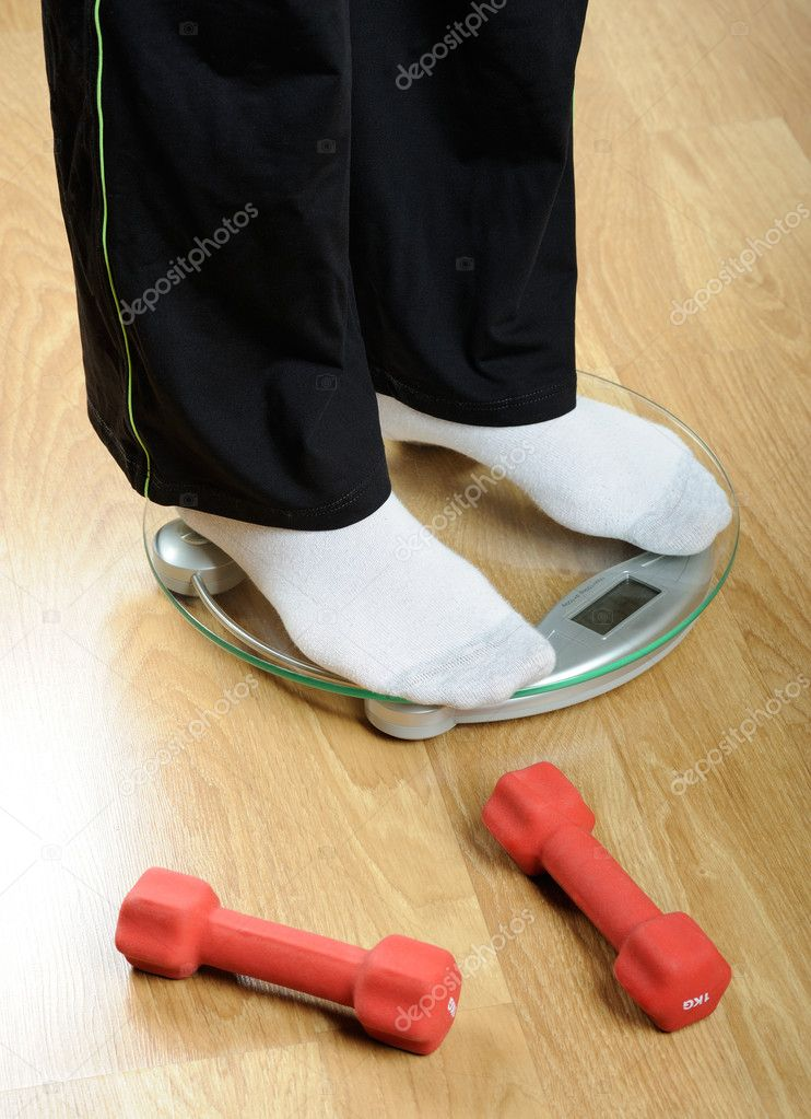 Woman`s feet standing on a weight scale on wooden floor — Stock Photo #1300677