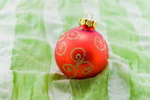 Christmas-tree ball on green textile — Stock Photo