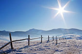 Wooden fence in snow covered mountains — Stock Photo