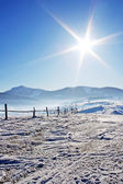 Fence in snow covered mountain under sky — Stock Photo