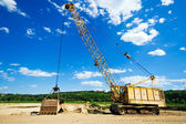 Old yellow excavator under blue sky — Stock Photo