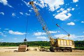 Old yellow excavator under blue sky — Stock Photo
