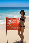 Woman with red flag on the sea — Stock Photo