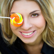 Woman with lollypop covering her eye — Stock Photo #1225359