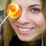 vrouw met lolly die betrekking hebben op haar oog — Stockfoto