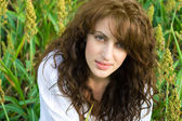 Woman in the field with wavy hair — Stock Photo