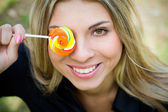 Woman with lollypop covering her eye — Stock Photo