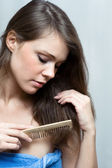 Attractive woman combing her hair — Stock Photo