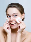 Woman cleaning face by cotton pad — Stock Photo