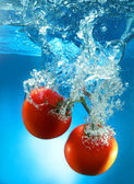 Isolated red tomatoes in water — Stock Photo