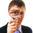 Young man looks through a magnifying glass — Stock Photo