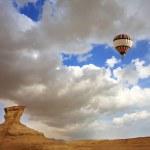 Huge balloon above mountains — Stock Photo