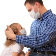 Family in medical masks with a thermomet — Stock Photo