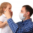 Stock Photo: Dad puts a medical mask on to daughter.