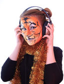 Girl a tiger in headsets listens music. — Stock Photo