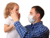 Dad puts a medical mask on to daughter. — Stock Photo