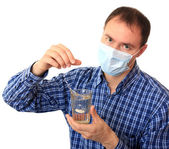 Man in a medical mask dissolves a pill — Stock Photo