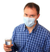 Man in a medical mask with water. — Stock Photo